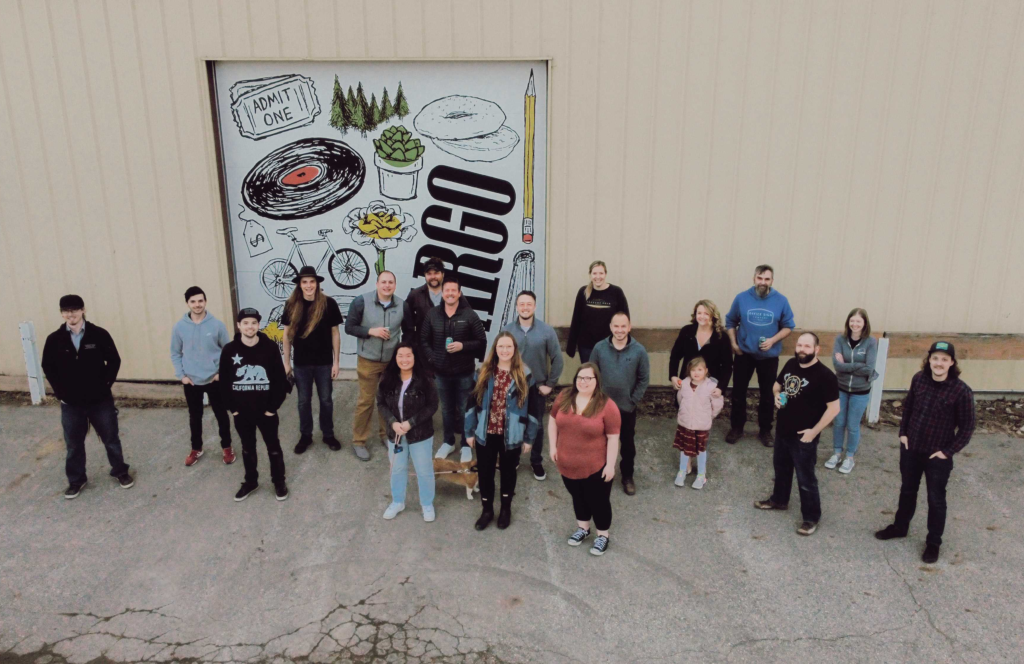This drone image is shot from above. Below, you can see 19 individuals from Office Sign Company smiling for the camera.